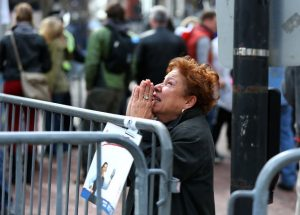 A woman kneels and prays at the scene of the first explosion on Boylston Street near the finish line of the 117th Boston Marathon on April 15, 2013. (Photo by John Tlumacki/The Boston Globe via Getty Images)